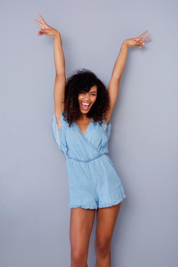 Den gladlynta unga afrikansk amerikankvinnan som skrattar med armar, lyftte mot den gråa väggen royaltyfria bilder