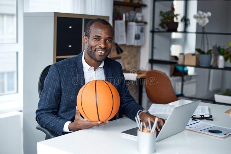 Den gladlynta unga chefen håller bollen och använder den smarta grejen royaltyfri fotografi