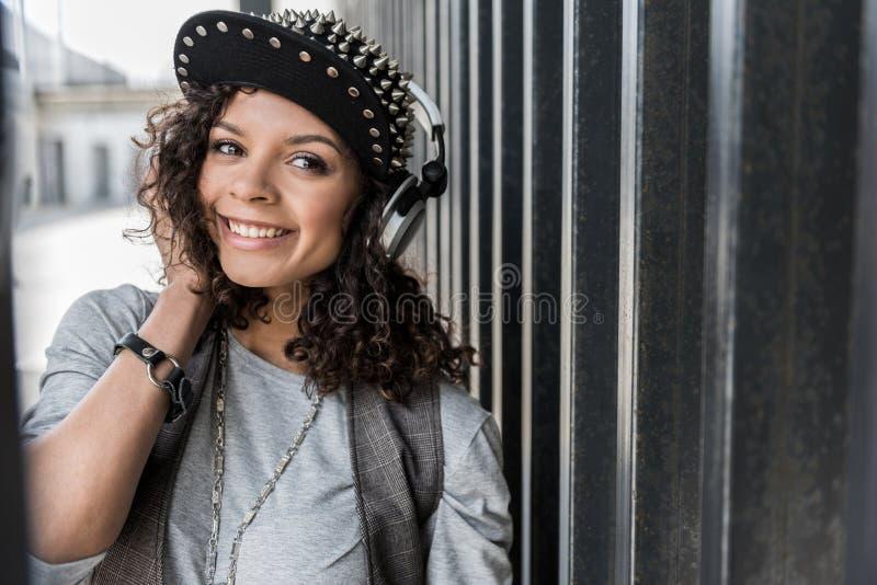 Den gladlynta unga hipsterkvinnlign står på gatan fotografering för bildbyråer