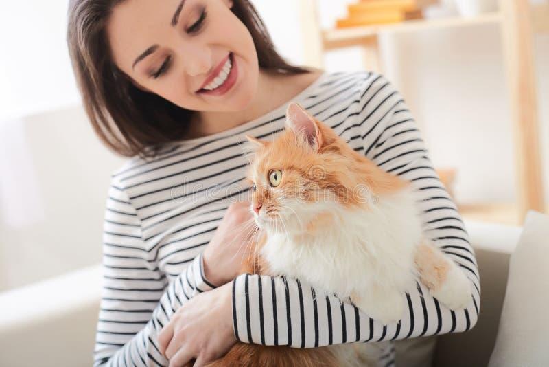 Den gladlynta unga kvinnan är avslappnande med djuret arkivfoton