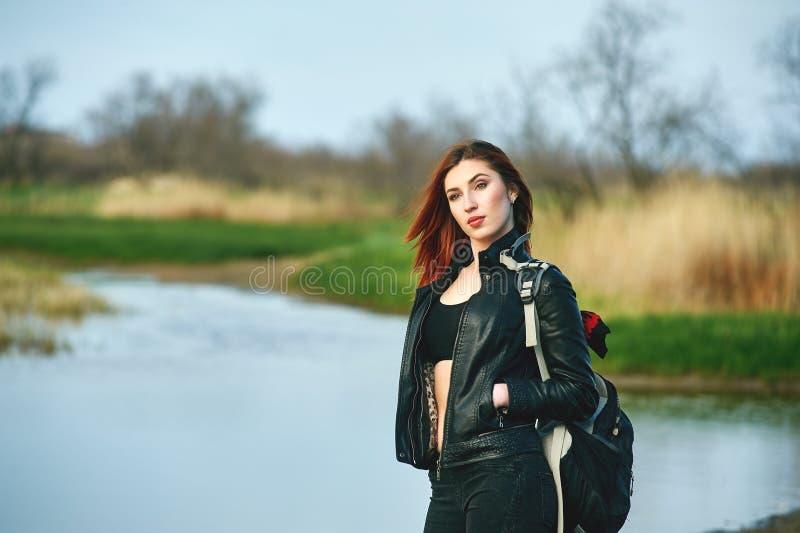 Den gladlynta unga kvinnan på våren går royaltyfria foton