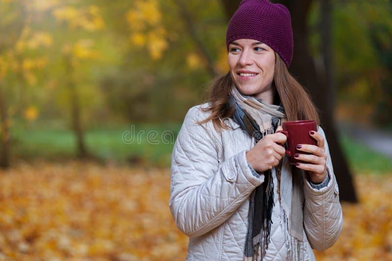 Den gladlynta unga kvinnan som tycker om nedgångnaturen parkerar in arkivbilder