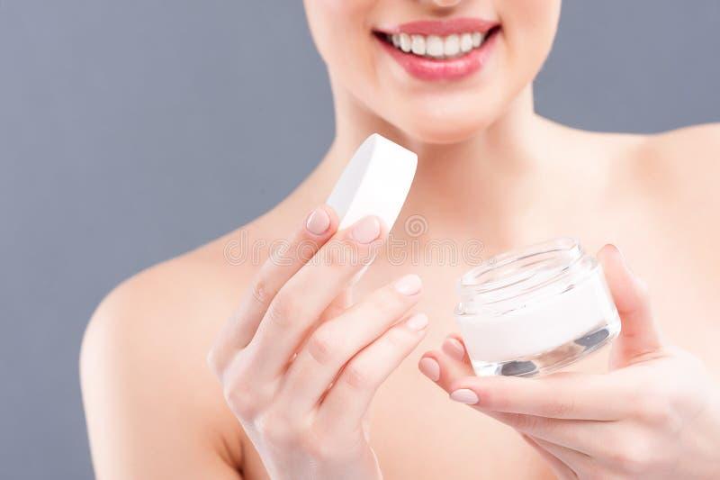 Den gladlynta unga kvinnan visar den kosmetiska produkten royaltyfria bilder