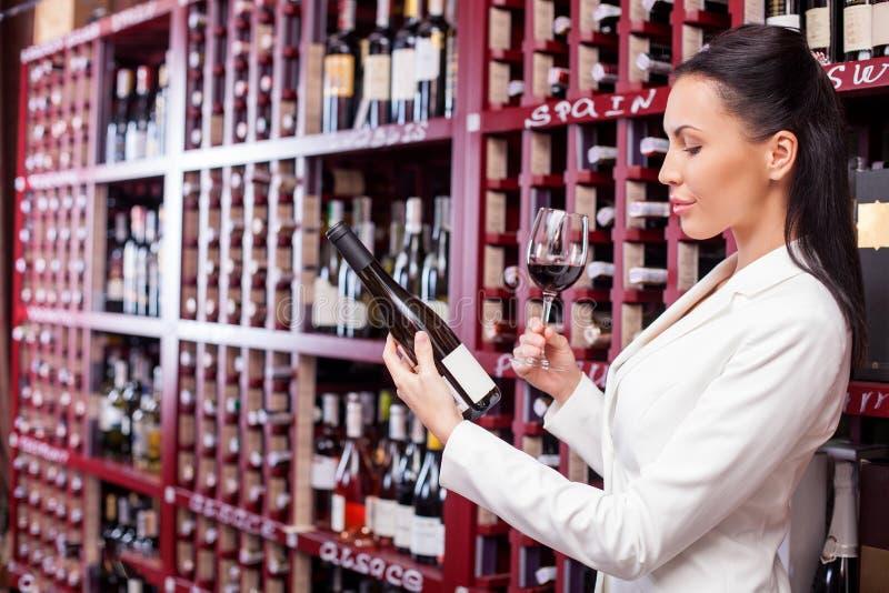 Den gladlynta unga kvinnliga vinhandlaren smakar alkohol royaltyfri foto