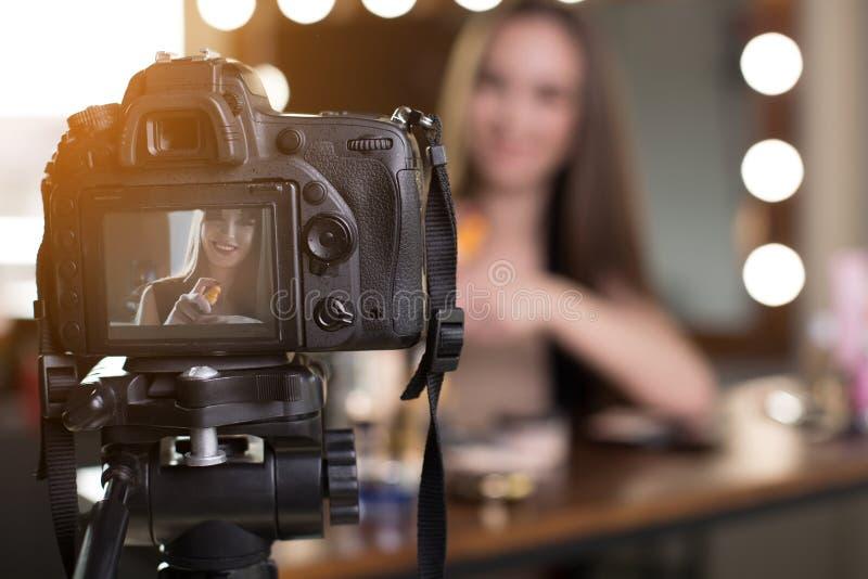 Den gladlynta unga kvinnlign filmar hennes skönhetblogg fotografering för bildbyråer