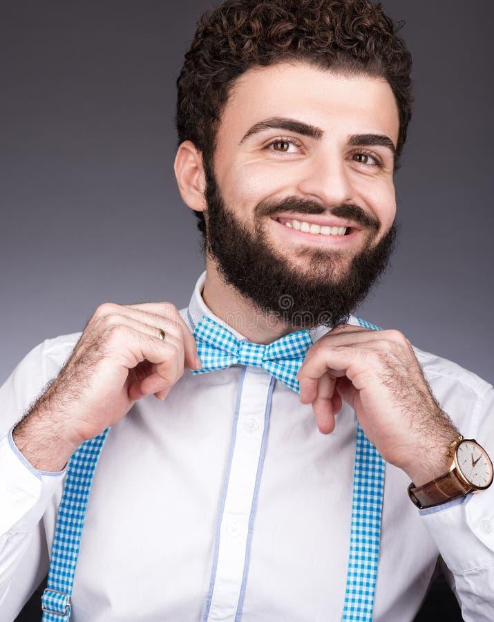 Den gladlynta unga mannen justerar hans fluga Mörkt lockigt hår, mustasch och skägg royaltyfria bilder