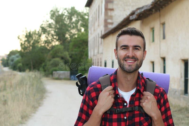 Den gladlynta unga mannen med skägget går till och med en liten europeisk stad med ryggsäcken royaltyfria bilder