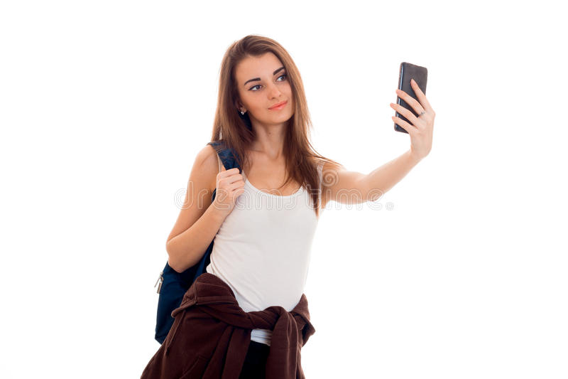 Den gladlynta unga studentflickan med ryggsäcken gör selfie på hennes mobiltelefon som isoleras på vit bakgrund studentår arkivfoto