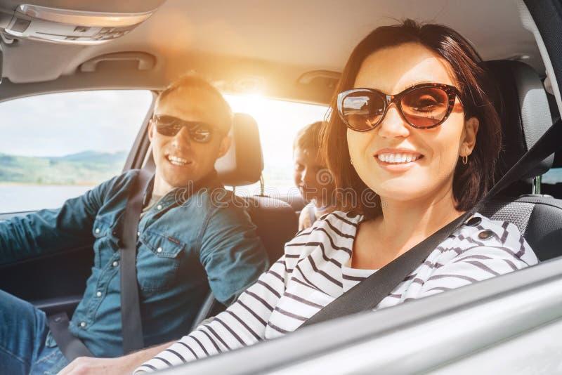 Den gladlynta unga traditionella familjen har en lång automatiskresa och att le tillsammans Begrepp för säkerhetsridningbil inom  royaltyfria bilder