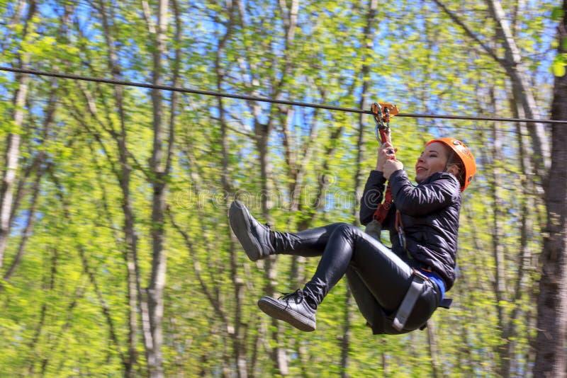 Den gladlynta unga turist- flickan stiger ned på Zipline arkivbilder