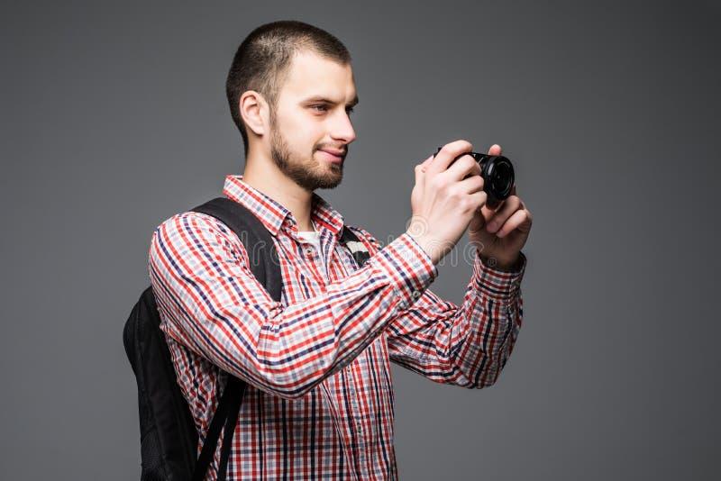 Den gladlynta unga turisten med ryggsäcken, den gamla fotokameran och smartphonen på selfie klibbar över grå bakgrund royaltyfri bild