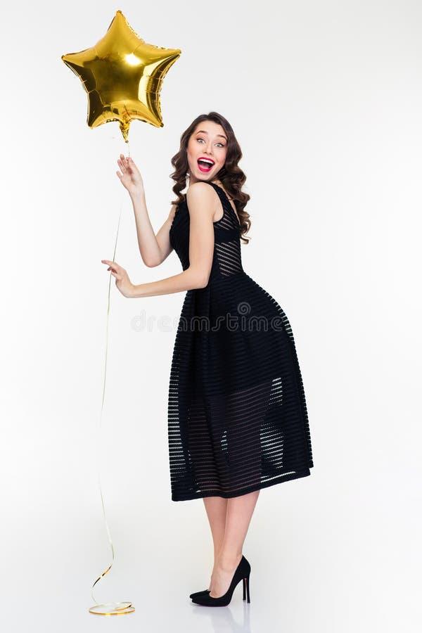 Den gladlynta upphetsade kvinnlign med den hållande stjärnan för den retro frisyren formade ballongen arkivfoton