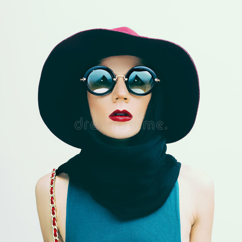 Den glamorösa damen i tappninghatt och solglasögon tenderar modeport royaltyfri foto