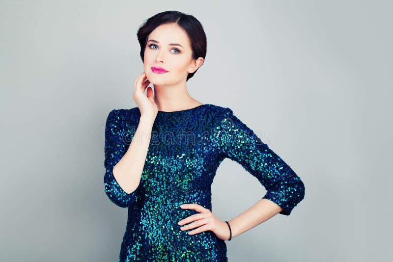 Den glamorösa kvinnan blänker in den trendiga klänningen fotografering för bildbyråer
