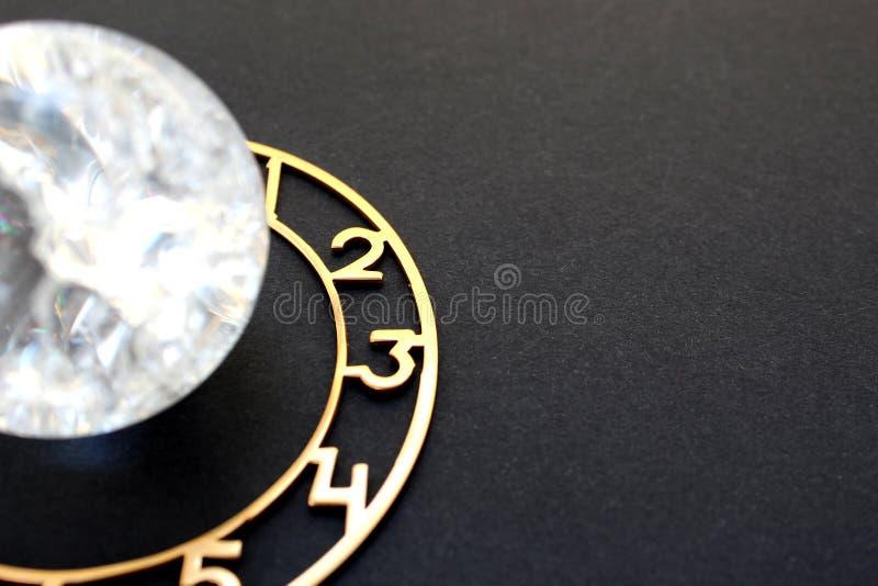 Den Glass bollen som omges av en visartavla, ligger på en svart bakgrund royaltyfri fotografi