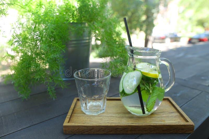 Den Glass karaffen och den exponeringsglas fasetterade koppen står på planka på tabellen in royaltyfri bild