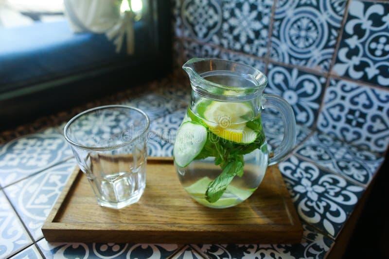 Den Glass karaffen och den exponeringsglas fasetterade koppen står på planka på tegelplattaintelligens arkivfoton