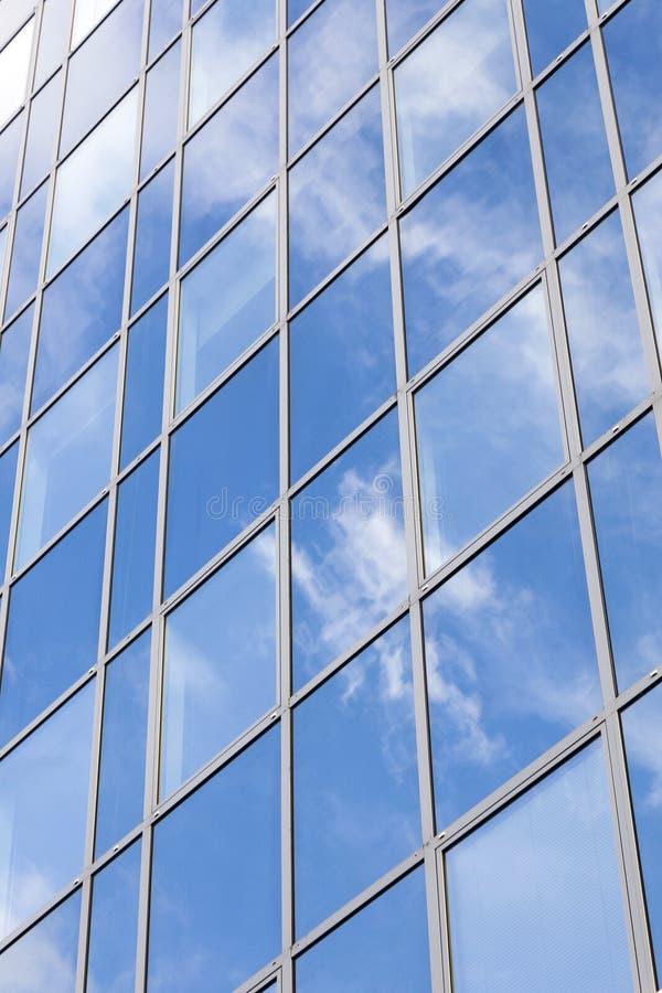 Den Glass kontorsfasaden reflekterar moln och blå himmel arkivfoton