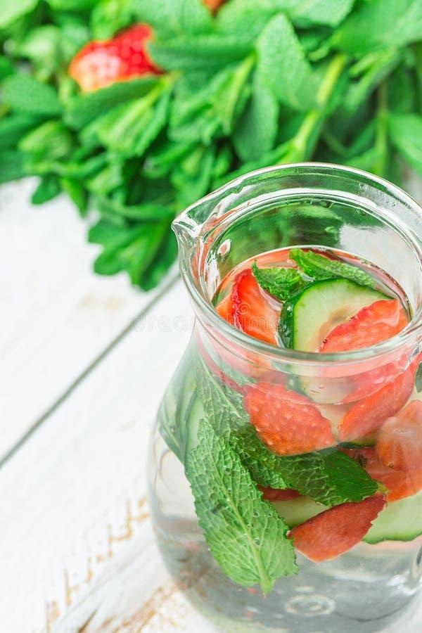 Den Glass tillbringaren med nytt kallt ingett Detoxvatten med mogna organiska jordgubbar skivade gurkamintkaramellen Vit plankatr fotografering för bildbyråer