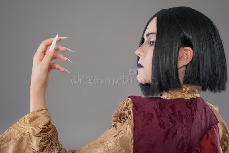 Den gotiska kvinnan med kines spikar royaltyfri fotografi
