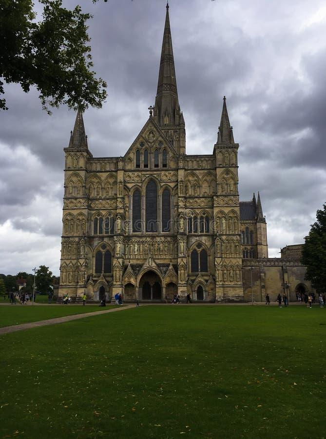 Den gotiska Salisbury domkyrkan på molnig dag och gräsplanen parkerar fotografering för bildbyråer