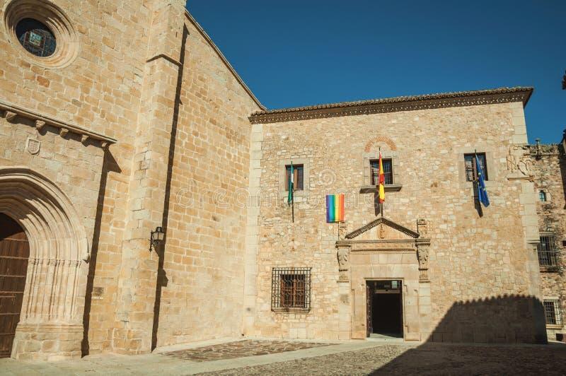 Den gotiska Santa Maria Cathedral och den gamla byggnaden med flaggor på Caceres arkivfoto