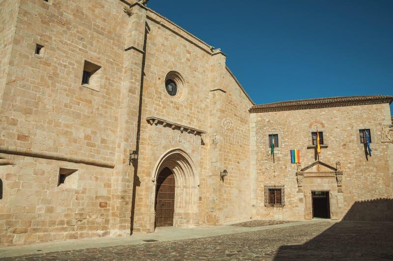 Den gotiska Santa Maria Cathedral och den gamla byggnaden med flaggor på Caceres arkivbild