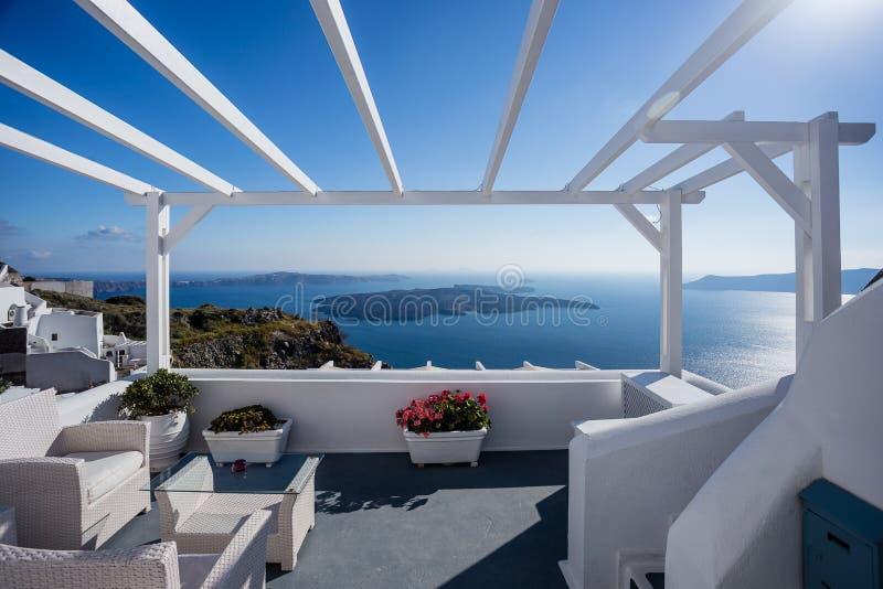 Den Gourgeous balkongsikten i vit walled semesterorten i Santorini, Grekland, med havet och klippor i bakgrunden royaltyfri fotografi