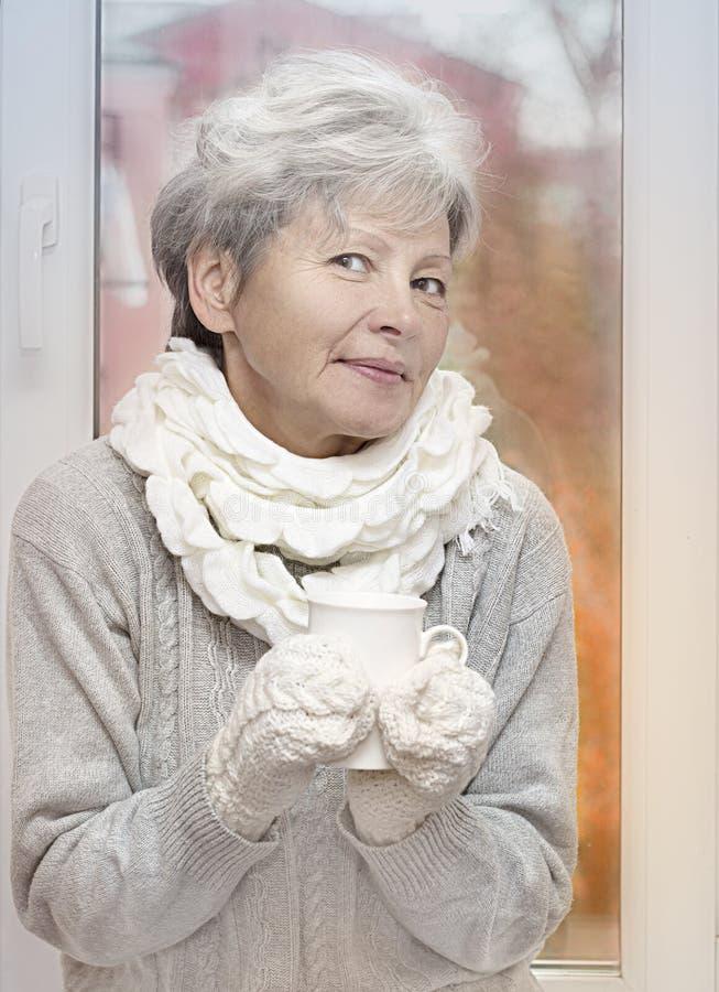 Den gråa haired kvinnan i vit stack järnhandskar dricker drycken och att le på höstfönsterbakgrund Äldre kvinna med arkivbild
