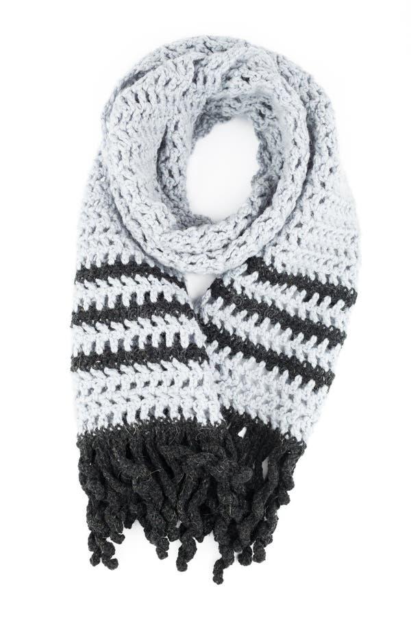 Den gråa halsduken av handwork stack vid en krok på en vit bakgrund royaltyfri fotografi