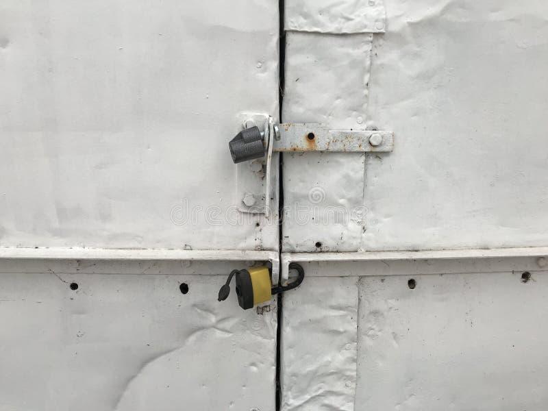 Den gråa metallgaragedörren låste Grov metallport på låsnärbild Grungebakgrund av den metalliska dörren med hänglåset royaltyfri bild