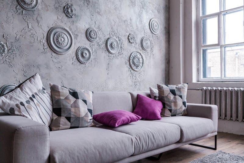 Den gråa moderna soffan står på bakgrunden av en vägg som dekoreras med stuckaturen arkivbild