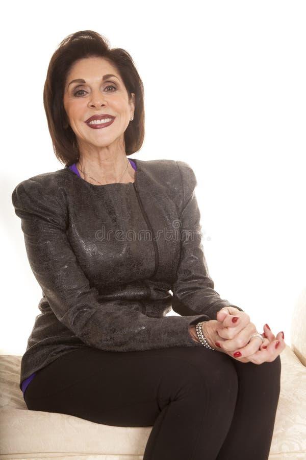 Den gråa omslagskvinnan sitter leende arkivbilder