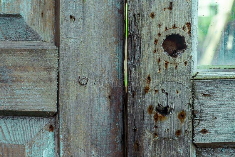 Den gråa trädörren med hål från låset och den rostiga fläcken från spikar Horisontalgrungetextur arkivfoton