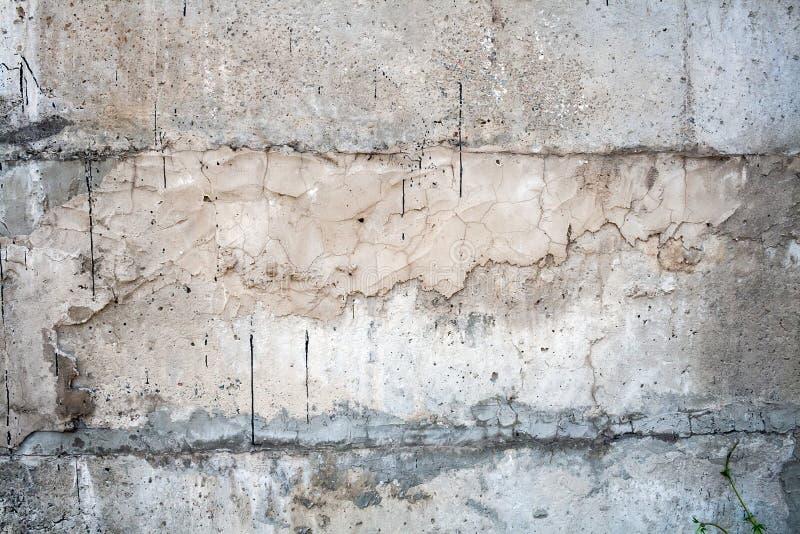 Den gråa väggen som täckas med ett ojämnt grovt lager av murbruk med hål, oriktigheter, sprickor och tunt, spårar av flödande sva arkivbild