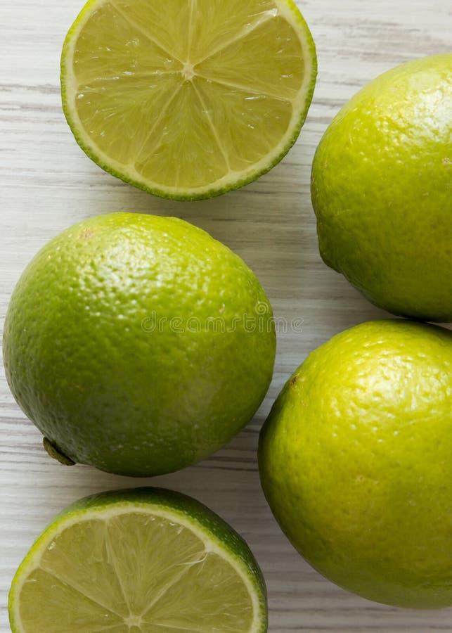 Den gröna citruns kalkar på en vit trätabell, över huvudet sikt Fr?n ?ver b?sta sikt, lekmanna- l?genhet N?rbild royaltyfria bilder