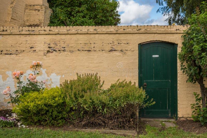 Den gröna dörren och guling red ut väggen i Richmond Tasmania Austra arkivfoton