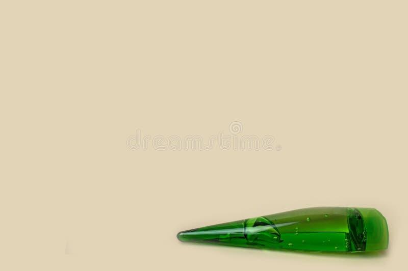 Den gröna flaskan med kosmetisk aloe stelnar på en gul bakgrund arkivbild