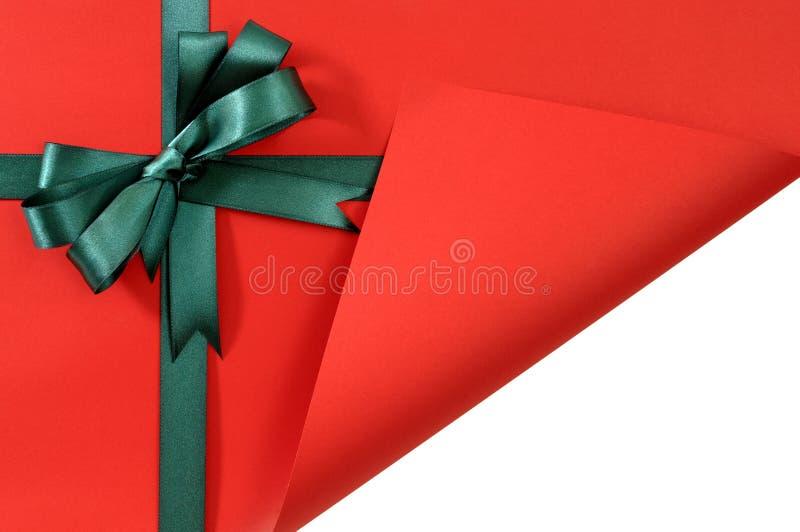 Den gröna gåvabandpilbågen på vanligt rött bakgrundspapper, hörn vek vitt kopieringsutrymme för den öppna visningen inom arkivbilder