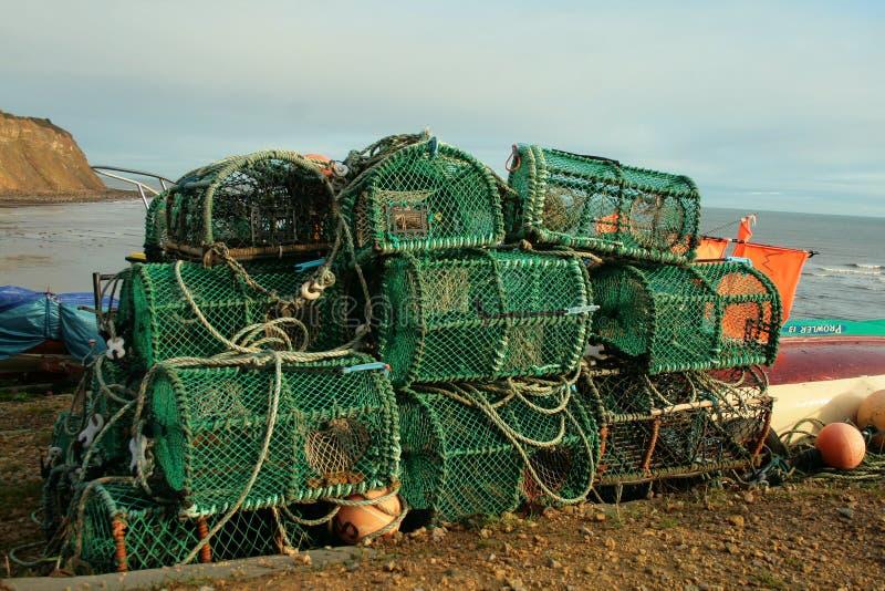Den gröna humret cages uttorkning på kust royaltyfri foto