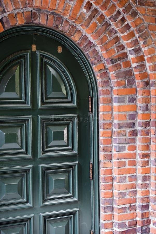 Den gröna ingången välva sig dörren som inramades av tegelstenbågen av byggnaden royaltyfria bilder