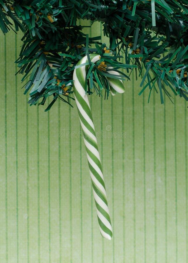 Den gröna karamellspiralen klibbar på filialen av den konstgjorda christmaen arkivfoto