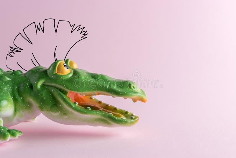 Den gröna krokodilen leker med att dra mohawk på pastellfärgad rosa bakgrund Minsta Art Concept arkivbild