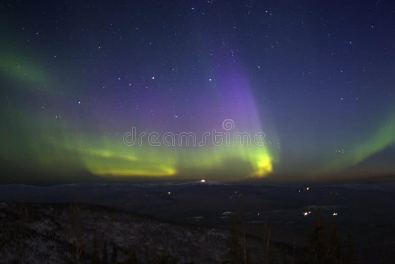 den gröna kullen tänder nordligt över gulaktig purpur sky starry t royaltyfria foton