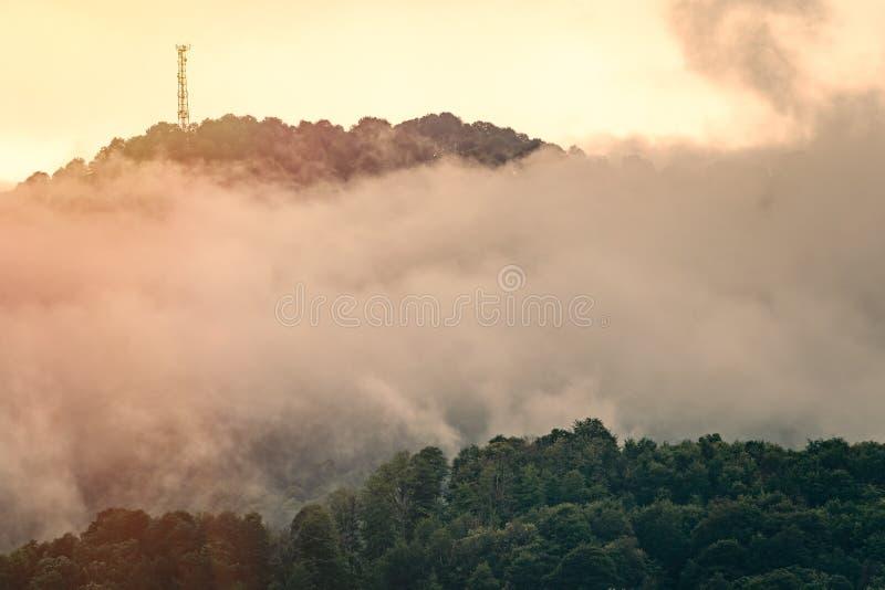 Den gröna lutningen av berget med kabelbilarna försvann i dimman solnedg?ng f?r orange f?r corfu greece ?berg royaltyfri foto