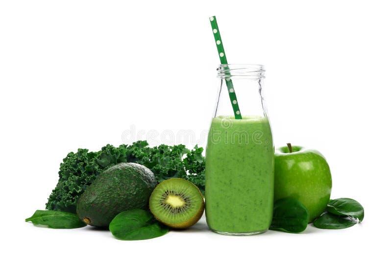 Den gröna smoothien mjölkar in flaskan med ingredienser som isoleras på vit arkivfoto