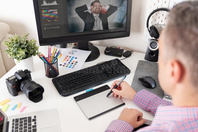 Den grafiska formgivaren använder en penna och en grafisk minnestavla royaltyfri fotografi