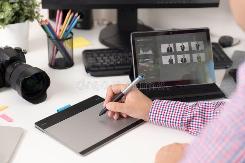 Den grafiska formgivaren använder en penna och en grafisk minnestavla arkivbild