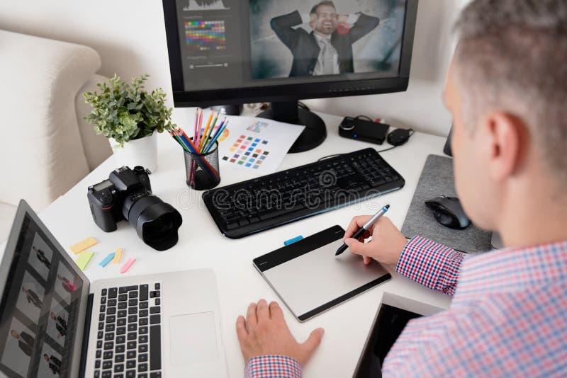 Den grafiska formgivaren använder en penna och en grafisk minnestavla royaltyfria foton