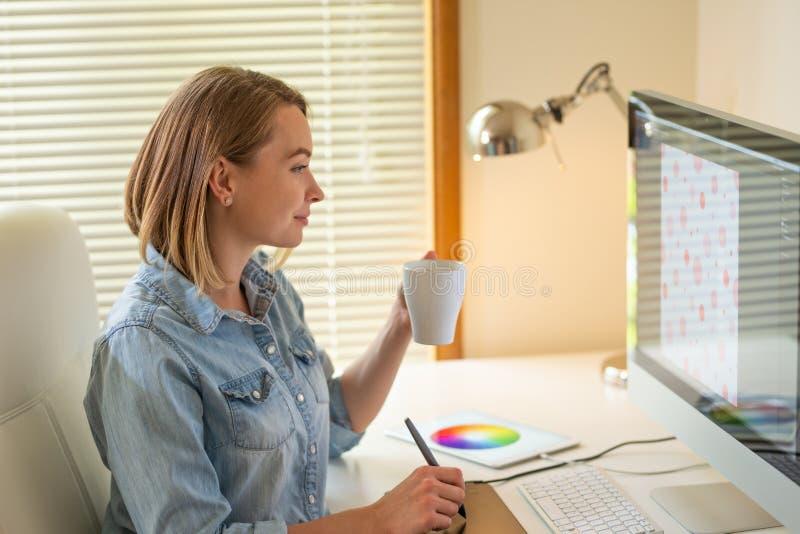Den grafiska formgivaren arbetar på en dator genom att använda en grafisk minnestavla på en tabell arbeta med rengöringsdukdesign arkivfoton